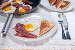 Eggs bacon and toast bread. Eggs sunny side up with bacon and toast typical english breakfast Royalty Free Stock Photos