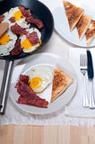 Eggs bacon and toast bread. Eggs sunny side up with bacon and toast typical english breakfast Stock Photo