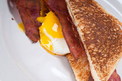 Eggs bacon and toast bread. Eggs sunny side up with bacon and toast typical english breakfast Stock Photos