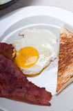Eggs bacon and toast bread. Eggs sunny side up with bacon and toast typical english breakfast Royalty Free Stock Photography
