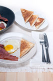 Eggs bacon and toast bread. Eggs sunny side up with bacon and toast typical english breakfast Royalty Free Stock Photo
