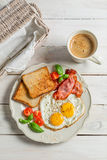 Eggs, bacon and toast for breakfast. On old wooden table Stock Photo