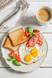 Eggs, bacon and toast for breakfast. On old wooden table Stock Image