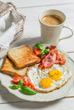 Eggs, bacon, toast and coffee for breakfast. On old wooden table Royalty Free Stock Photography