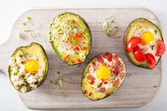 Eggs baked in avocado with bacon, cheese, tomato and alfalfa sprouts royalty free stock image