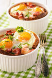 Eggs baked with bacon, tomatoes, garlic and bread. Stock Photos