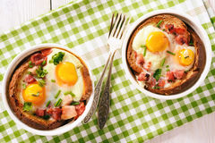 Eggs baked with bacon, tomatoes, garlic and bread. Royalty Free Stock Images