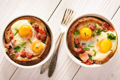 Eggs baked with bacon, tomatoes, garlic and bread. Eggs baked with bacon, tomatoes, garlic and bread Stock Photos