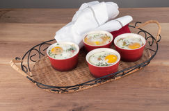 Eggs baked with creamy sauce, mushrooms, ham, cheese and herbs i Royalty Free Stock Photography