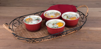 Eggs baked with creamy sauce, mushrooms, ham, cheese and herbs i Royalty Free Stock Photos