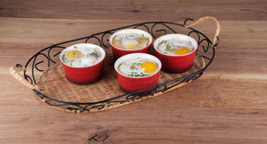 Eggs baked with creamy sauce, mushrooms, ham, cheese and herbs i Royalty Free Stock Images