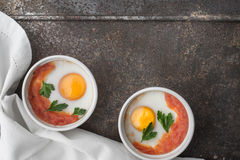 Eggs baked with tomatoes and parsley in the ramekins on the metal background top view Stock Photo