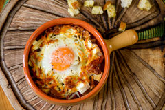 Eggs baked with vegetables and crackers. Eggs baked with vegetables and croutons in a clay pot Stock Images