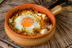 Eggs baked with vegetables and crackers. Eggs baked with vegetables and croutons in a clay pot Royalty Free Stock Photography