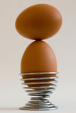 Eggs balancing in eggcup. Two eggs balancing in steel spring shaped eggcup, put on grey background Stock Photos