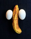 Eggs and banana composing a penis  on wood Stock Photography
