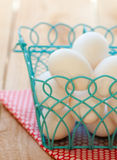 Eggs in a basket. A pile of white eggs sit in a blue wire basket on top of a red polka dot napkin on a wooden farm table Stock Photo
