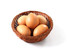 Eggs basket. Raw fresh eggs in a basket over white Royalty Free Stock Images