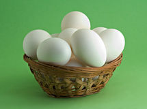 Eggs in basket. Isolated on green background Stock Images