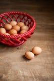 Eggs in a basket. Brown farm eggs in basket, wood floor, red basket, wooden floor Royalty Free Stock Image