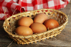 Eggs in basket on brown wooden background. Royalty Free Stock Image