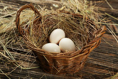 Eggs in basket on brown wooden background. Stock Photography