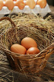Eggs in basket on a brown wooden background Royalty Free Stock Images