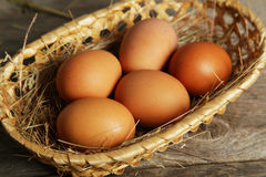 Eggs in basket on a brown wooden background Stock Image