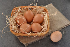Eggs in a basket on grey background. Eggs in a small basket on grey background stock image