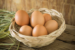 Eggs on basket. Eggs on basket with hay on wooden background Stock Images