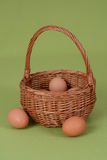 Eggs in the basket. Hen egg in a wicker basket on a green tablecloth Royalty Free Stock Photo