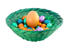 Eggs in basket. Isolated fresh and chocolate eggs in a green basket Royalty Free Stock Images