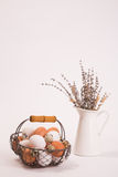 Eggs in a basket and lavender in a cup. Different kinds of eggs in an old basket with a wooden handle and a white metal vase with lavender flowers on a white Stock Image