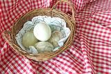 Eggs In A Basket. This photo shows some marble and onyx eggs in a wicker basket and on a red gingham background royalty free stock image