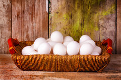 Eggs on a basket with a rustic wood  background Royalty Free Stock Photo
