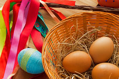 Eggs in a basket, tables and Easter whip. Stock Photo