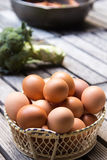 Eggs in basket and vegetables Stock Photo