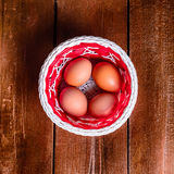 Eggs in the basket on wood texture Stock Photos