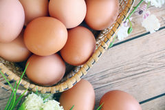 Eggs in the basket. On wooden background Stock Photos