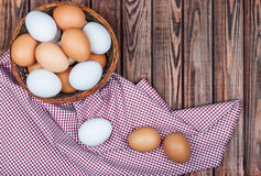 Eggs in basket. On a wooden background Royalty Free Stock Photo