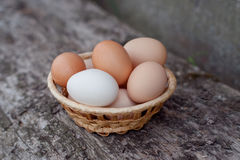 Eggs in a basket on a wooden background. Eggs lying in a basket on a wooden background stock photos