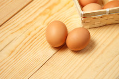 Eggs in a basket on a wooden table background. Royalty Free Stock Image