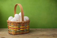 Eggs in basket on wooden table over green background Royalty Free Stock Photos