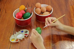 Eggs are being painted by hands of young christian man with paintbrust prepare for easter time. Stock Photography