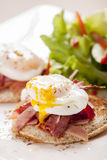 Eggs Benedict. Poached egg on toast, with smoked bacon, and salad Royalty Free Stock Images