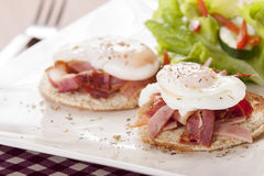 Eggs Benedict. Poached egg on toast, with smoked bacon, and salad stock images