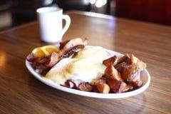 Eggs benedict, bacon, and potatoes stock photo