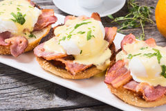 Eggs benedict with bacon. On wooden background royalty free stock photos