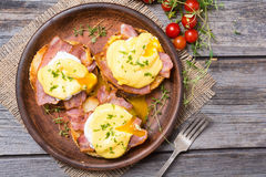 Eggs benedict with bacon. On wooden background . Top view . Space for text stock images