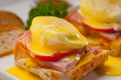 Eggs benedict on bread with tomato and ham Royalty Free Stock Photos